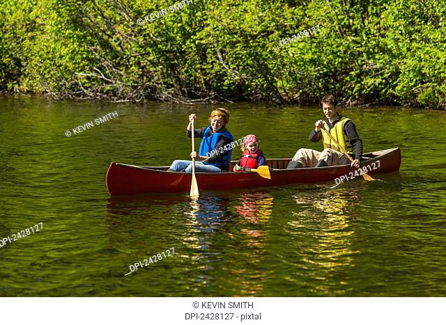 A couple and young girl in a red canoe on Byers lake with green forested shoreline in Byers Lake Campground, Denali State Park; Alaska, United States of America