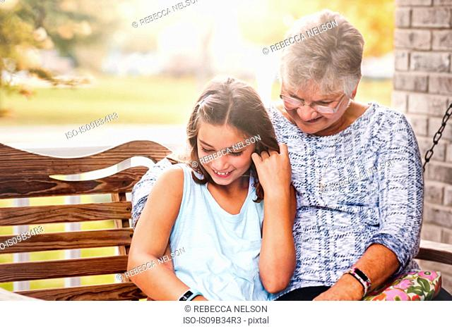 Grandmother and granddaughter sitting on porch swing, laughing
