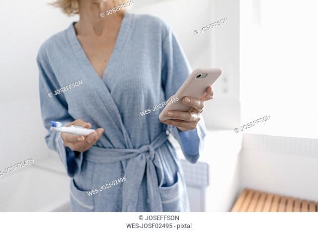 Close-up of woman with cell phone and toothbrush in bathroom