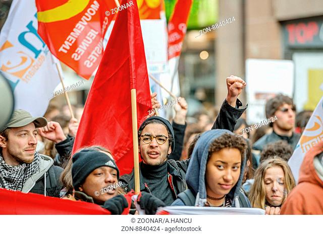STRASBOURG, FRANCE - 9 MAR 2016: Protester with rised hands in front row of thousands of people demonstrating as part of nationwide day of protest against...