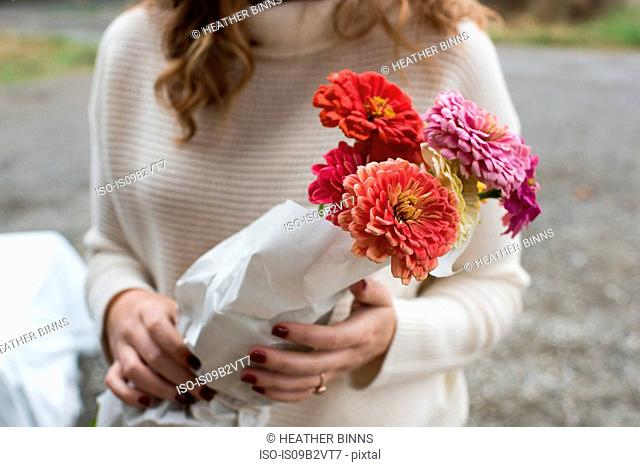 Mid section of woman holding bunch of flowers at organic farm shop