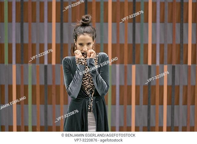 portrait of confident fashionable woman, playing with clothes, hiding, in front of geometrical line pattern, in Munich, Germany