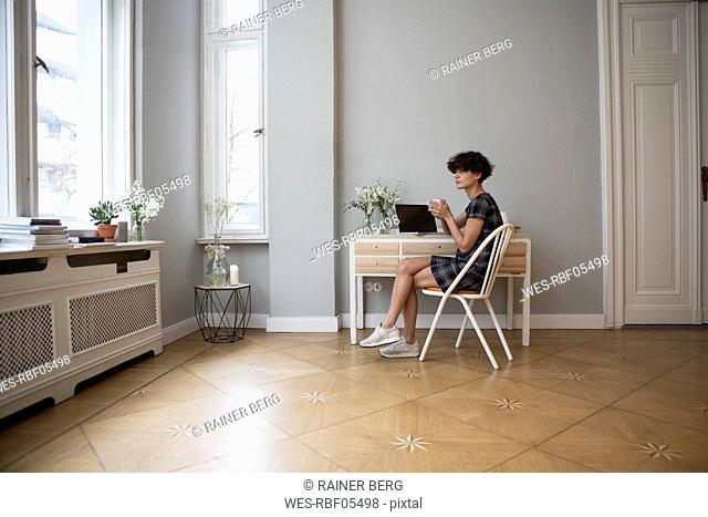 Young woman sitting at desk at home with cup of coffee looking through window