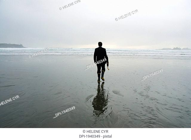 a man walking on a wet beach holding an umbrella, tofino british columbia canada