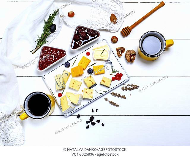cheese board with raspberry and strawberry jam, side by side two yellow ceramic cups with black coffee, white wooden background, top view