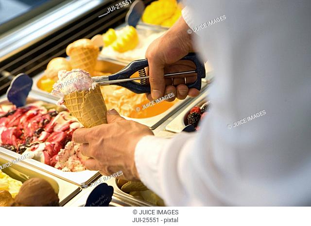 Man filling ice cream cone with ice cream