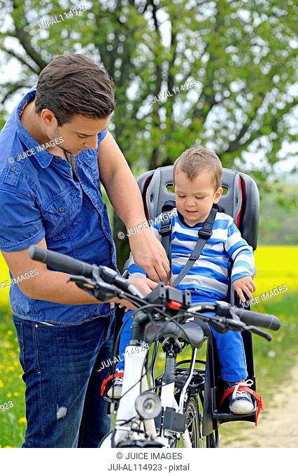 Young man securing son's child seat on bicycle