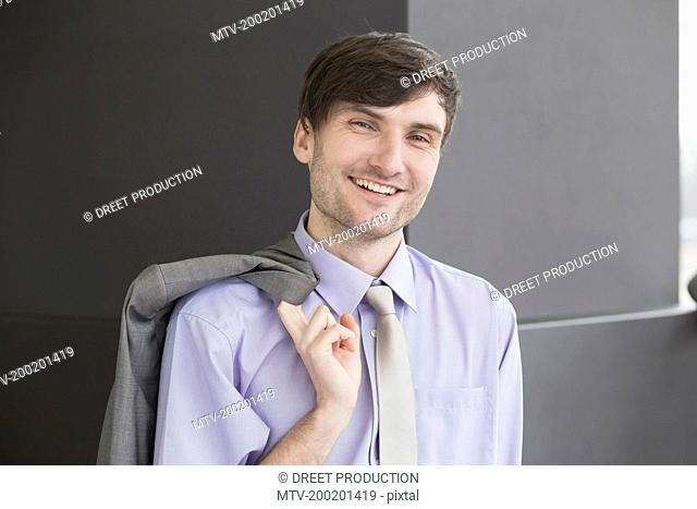 Portrait of businessman holding suit, smiling