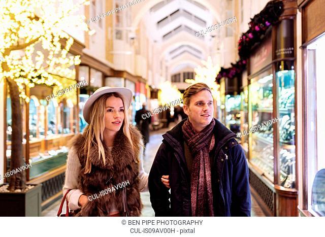 Young couple shopping in Burlington Arcade at xmas, London, UK