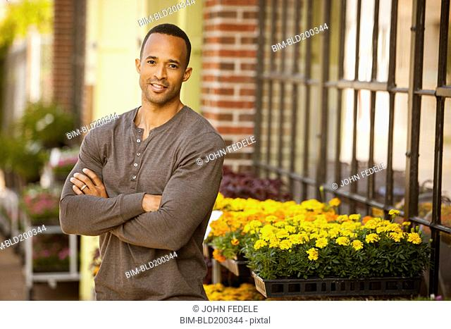 African American man standing near flower shop
