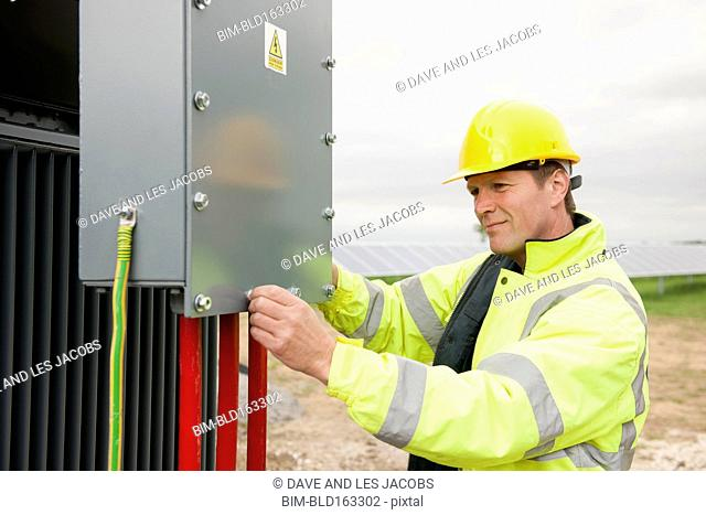 Caucasian technician examining industrial control panel