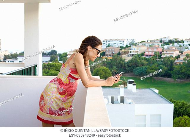 adult woman, with red dress and sunglasses, watching or using smartphone in the terrace. Behind green nature and houses