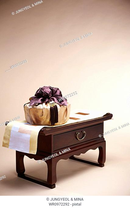 a package in Korean traditional wrap placed on a traditional table