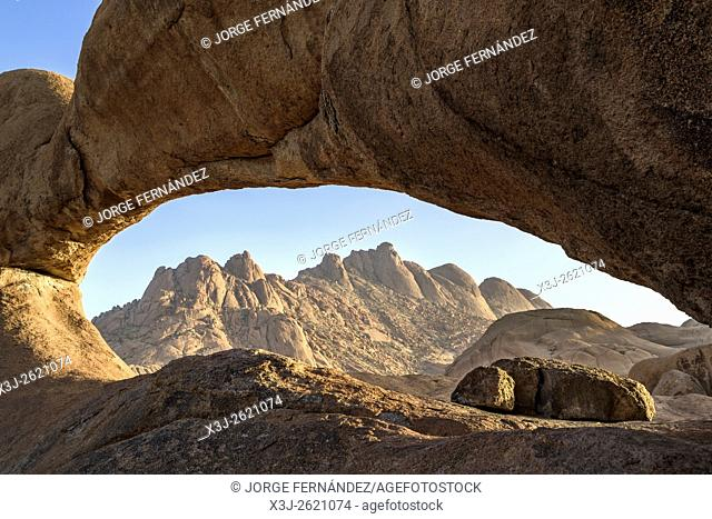 View of the Pontoc mountains near the famous Spitzkoppe, through a stone arch early in the morning