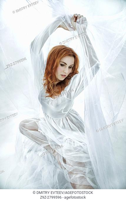 Redhair maiden in white tissut in abstact surroundings