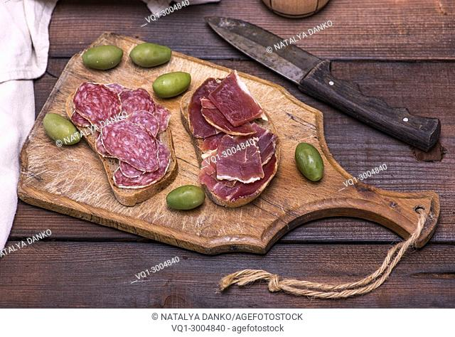 sandwiches with salami sausage and hamon on a brown wooden board