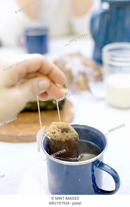Close up of a hand removing a teabag from a mug of tea