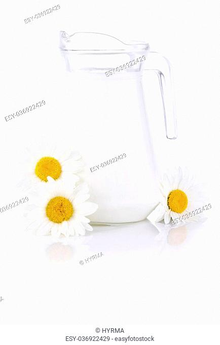 Jug fresh milk and three chamomile flowers isolated on white background