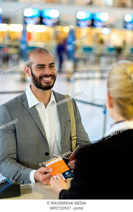 Airline check-in attendant handing boarding pass to commuter