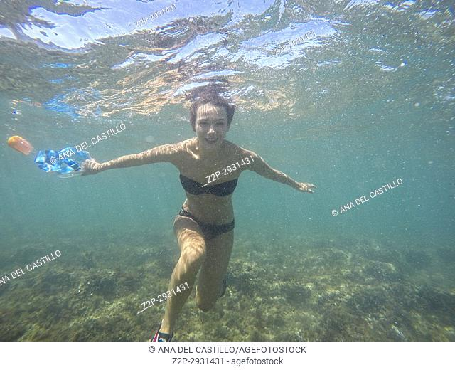 Underwater image with young woman in Las Rotas nature reserve Denia Alicante Spain