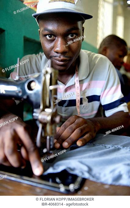 Young man working on a sewing machine learning tailoring crafts, tailoring school of the Salesian Missions, Salesian project at Lakou, La Saline quarter