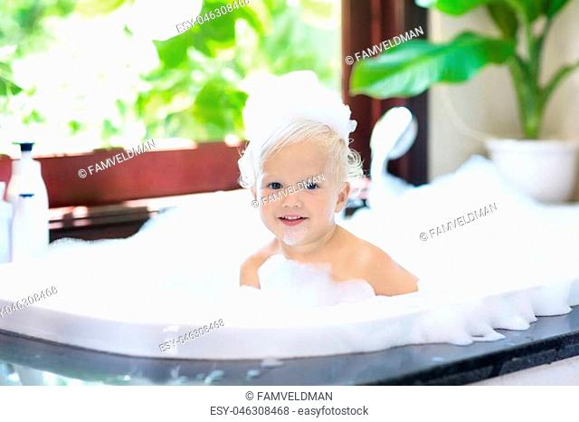 Little child taking bubble bath in beautiful bathroom with big garden view window. Kids hygiene. Shampoo, hair treatment and soap for children