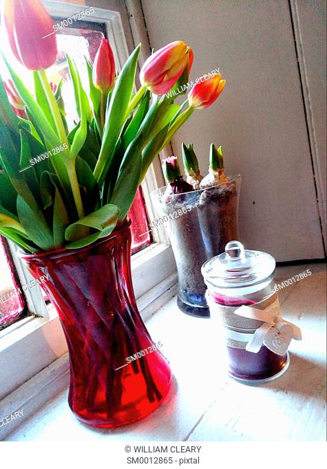Tulips in a red vase and a candle in a jar with a heart decoration