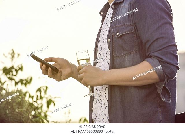 Man with glass of champagne using mobile phone