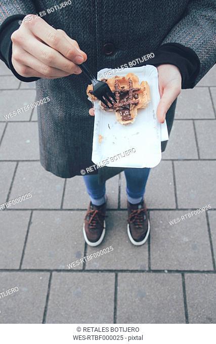 Belgium, Antwerp, young man eating Belgian waffles on the street