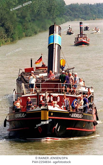 """with slightly flattened chimney in front of a bridge leads on August 4, 1999 at Wunstorf the steam tug """"""""Andreas"""""""" a convoy of historic ships on the withtelland..."""