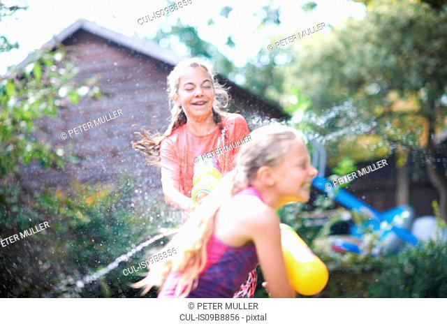 Teenage girl and her sister squirting water guns at each other in garden