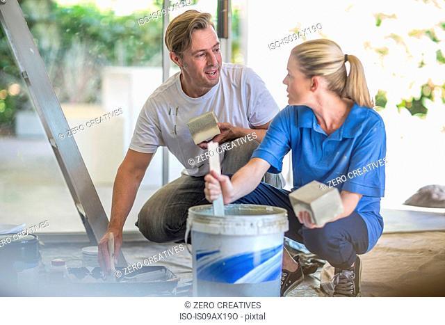 Couple crouching stirring bucket of paint
