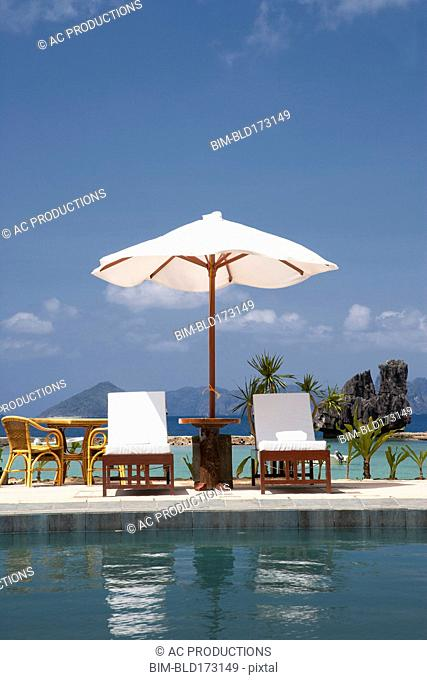 Lawn chair and umbrella at swimming pool