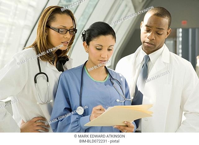 Multi-ethnic doctors and nurse reviewing medical chart