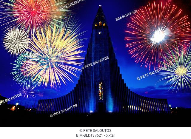 Fireworks exploding over monument in night sky, Reykjavik, Hofudborgarsvaedi, Iceland