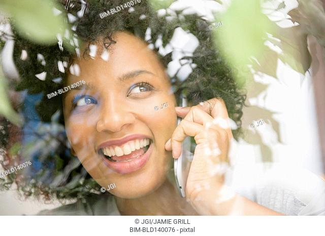 Smiling woman talking on cell phone near window