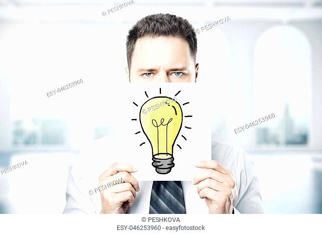 Businessman covering face with light bulb drawn on paper sheet. Idea concept