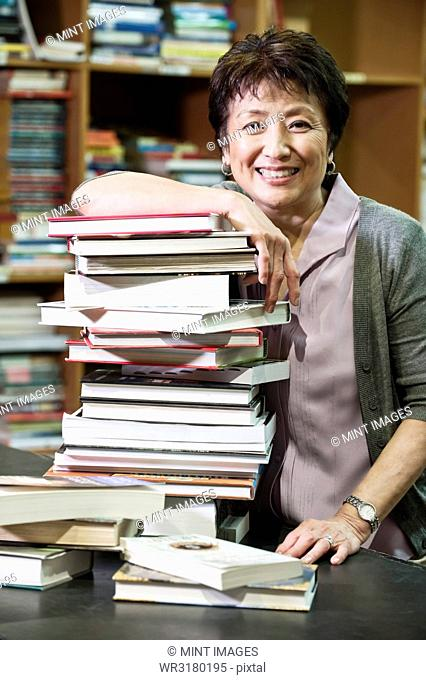Portrait of an Asian American female owner of a bookstore leaning on a large stack of books
