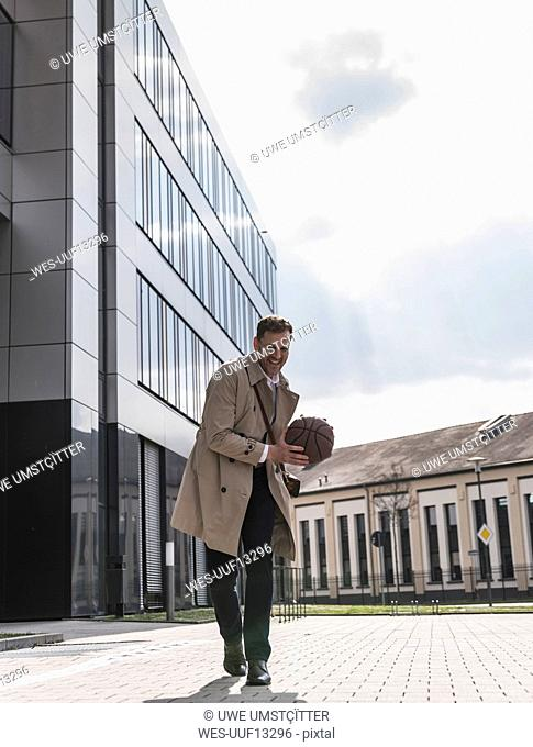 Happy businessman playing basketball outside office building