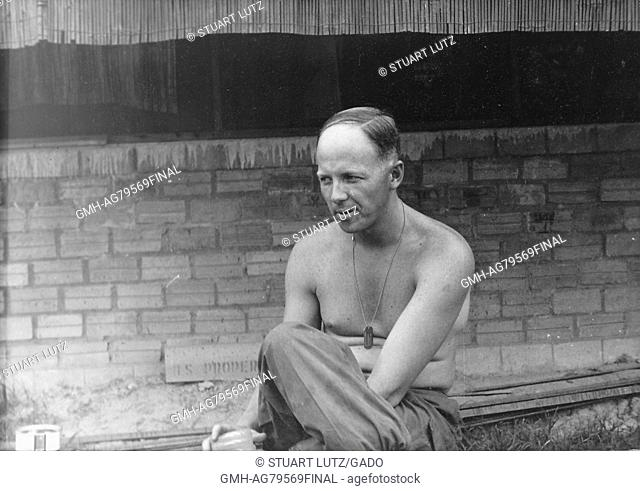 A shirtless United States Army serviceman sitting on a low wall, behind him there is a low masonry wall of a building that is open to the elements, Vietnam