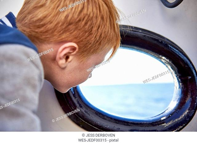 Boy looking out of the porthole