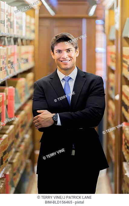 Hispanic businessman smiling in library