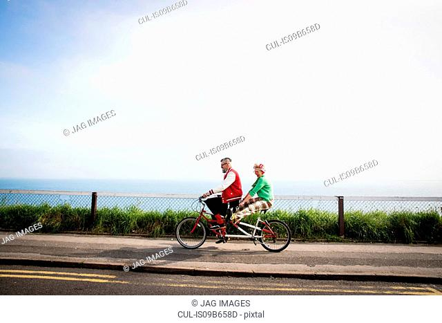 Quirky couple sightseeing on tandem bicycle, Bournemouth, England