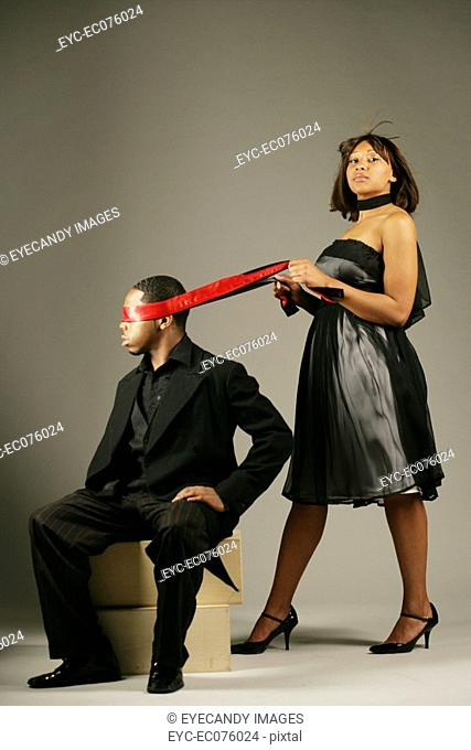 Young African American woman blindfolding man