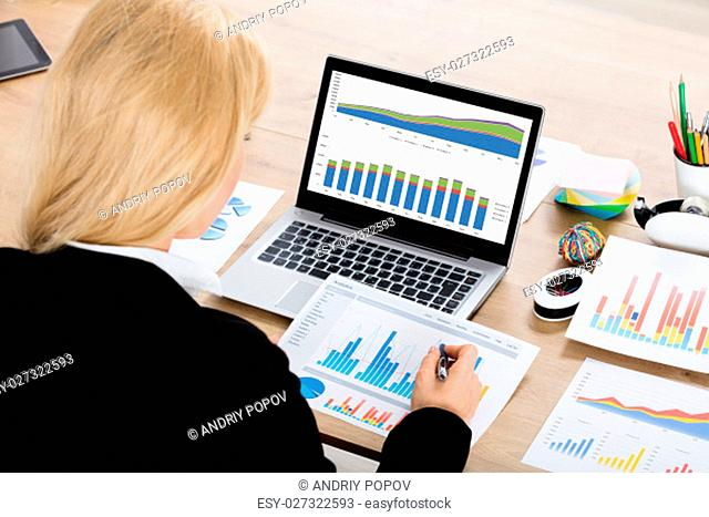 Close-up Of A Young Businesswoman Analyzing Financial Graphs At Workplace