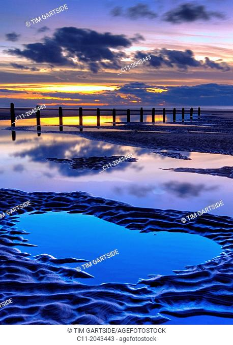 beach and wooden groyne at sunset, with large pools of water and cloud reflections, blackpool, lancashire, england, uk,europe