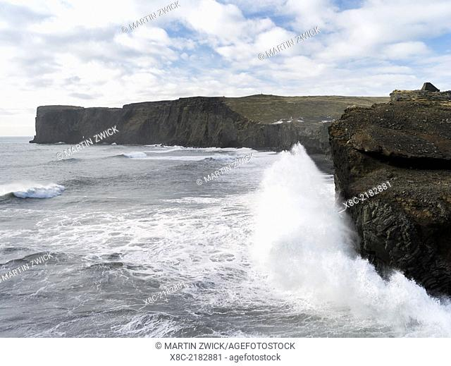Coast of the North Atlantic near Vik y Myrdal during a winter storm, view towards the stacks and sea arch at cape Dyrholaey