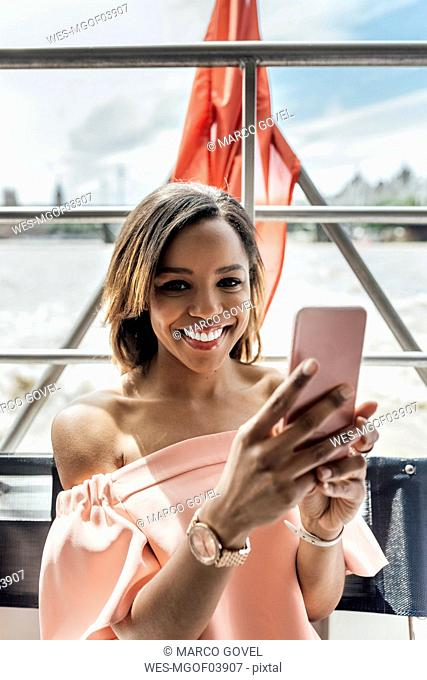 UK, London, portrait of beautiful smiling woman holding cell phone while traveling by boat on the River Thames