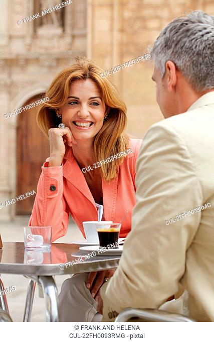 Smiling woman with coffee in cafe