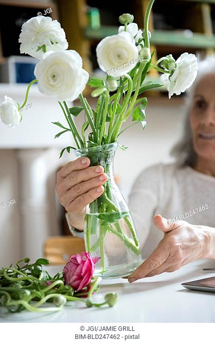 Older woman arranging flowers